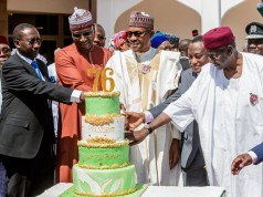 President Muhammadu Buhari...being assisted to cut his birthday cake by aides...