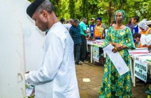 Vice President Yemi Osinbajo casts his vote...while his wife, Dolapo looks on...