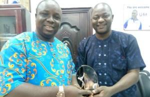 Asiwaju Ayinla Oladimeji, left, presenting the award to Evg Ajibola Ogunkeyede of UfitFly