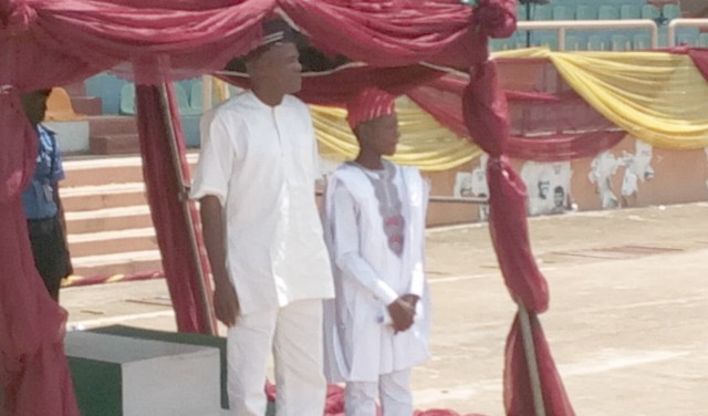Mr. Michael Awopetu, the Hon. Commissioner for Youth and Sports in Ekiti State who represented the Ekiti State Executive Governor, Dr. Kayode Fayemi while taking salute at the 2019 Children's Day Celebrations in Ado Ekiti and Rt. Hon. Michael Adebanji, the Hon. Speaker for Ekiti State Children's Parliament standing beside the Governor's representative at Eyitayo Pavillon, New Iyin Ekiti road...