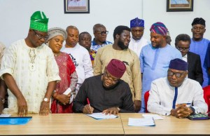Governor Kayode Fayemi...signs...while others look on...