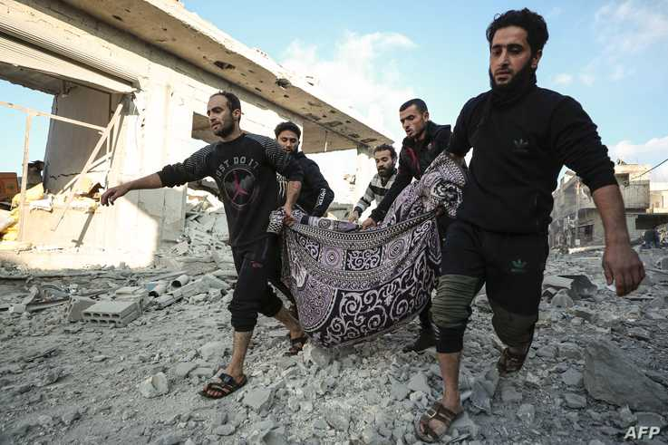 Syrian men carry a victim after a reported Russian airstrike on a popular market in the village of Balyun in Syria's…