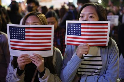 Protester holds U.S. flags during a demonstration in Hong Kong, Thursday, Nov. 28, 2019. China's fury over President Donald…