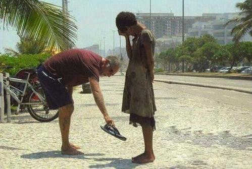 man-giving-poor-chid-shoes