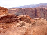 The slickrock plateau is formed of fractured, angled sandstone strata, eroded into small cliffs, mounds and gullies.