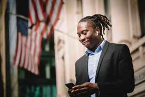 positive young black entrepreneur using mobile on street and smiling