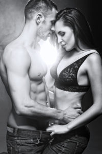 BW image of half-clothed couple looking down at their bodies