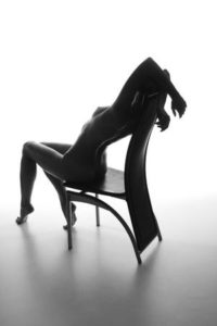 B/W silhouette of naked woman arching in chair