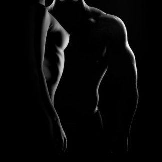 Silhouetted b/w image of topless couple close