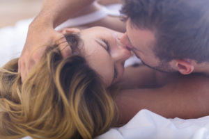 Photo of couple laying on sides kissing passionately