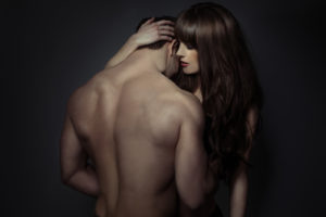 Tender moment lovers holding each other in a close intimate embrace , view from behind the bare back of the man