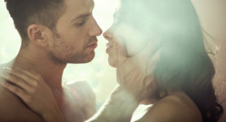 Young couple man cupping her cheek with light over her face about to kiss