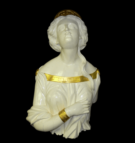 A bust/figurehead of a woman looking skywards with gold detail on collar, cuffs and crown.