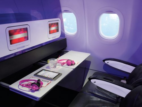 Forget about those obnoxious and filthy armrest tray tables. Virgin built its bulkhead IFE screens and tray tables into a translucent cabin divider. To all other airlines: this is the only acceptable way to do this. (Image courtesy Virgin America)