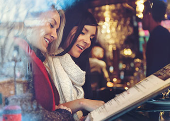 Point of Sale Two Women Looking at Holiday Menu Black Friday Restaurant Promotions
