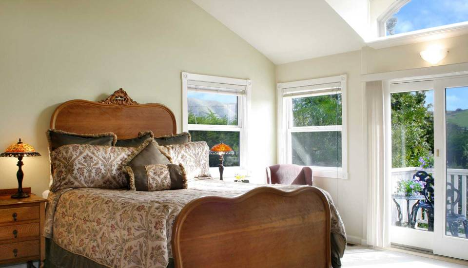Satinwood room with large bed and natural light from windows.