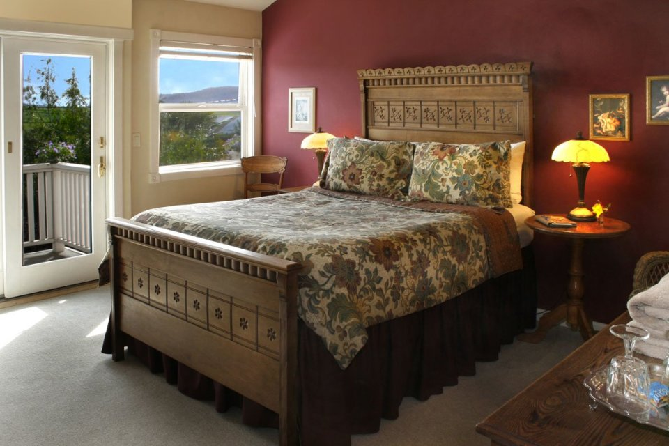 Inside view of room with private balcony, country views and large bed.