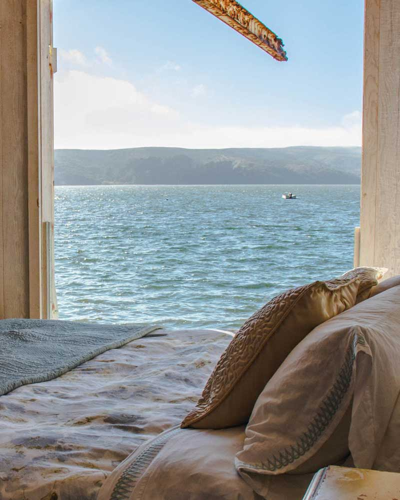 View of Tomales bay from a bed with pillows.