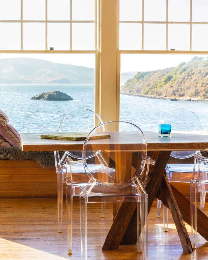 Dining room chairs and table with views of the bay through big windows.