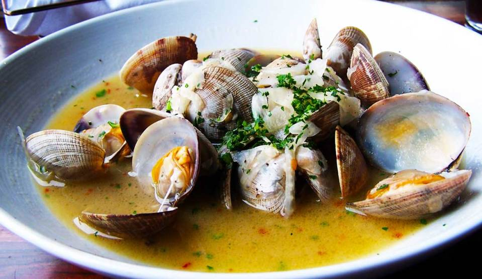 Bowl of steamed clams in broth.