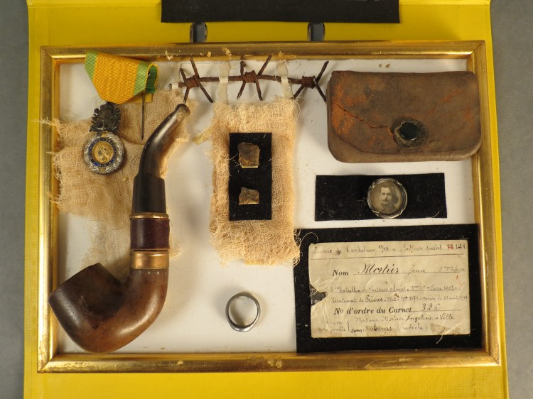 These are the personal effects of French soldier Camille Mortier. He was killed on August 21st, 1917. The shadow box contains Mortier's pipe, his wedding ring, and pieces of shrapnel that may have killed him. Source: http://www.europeana1914-1918.eu/en/contributions/12869