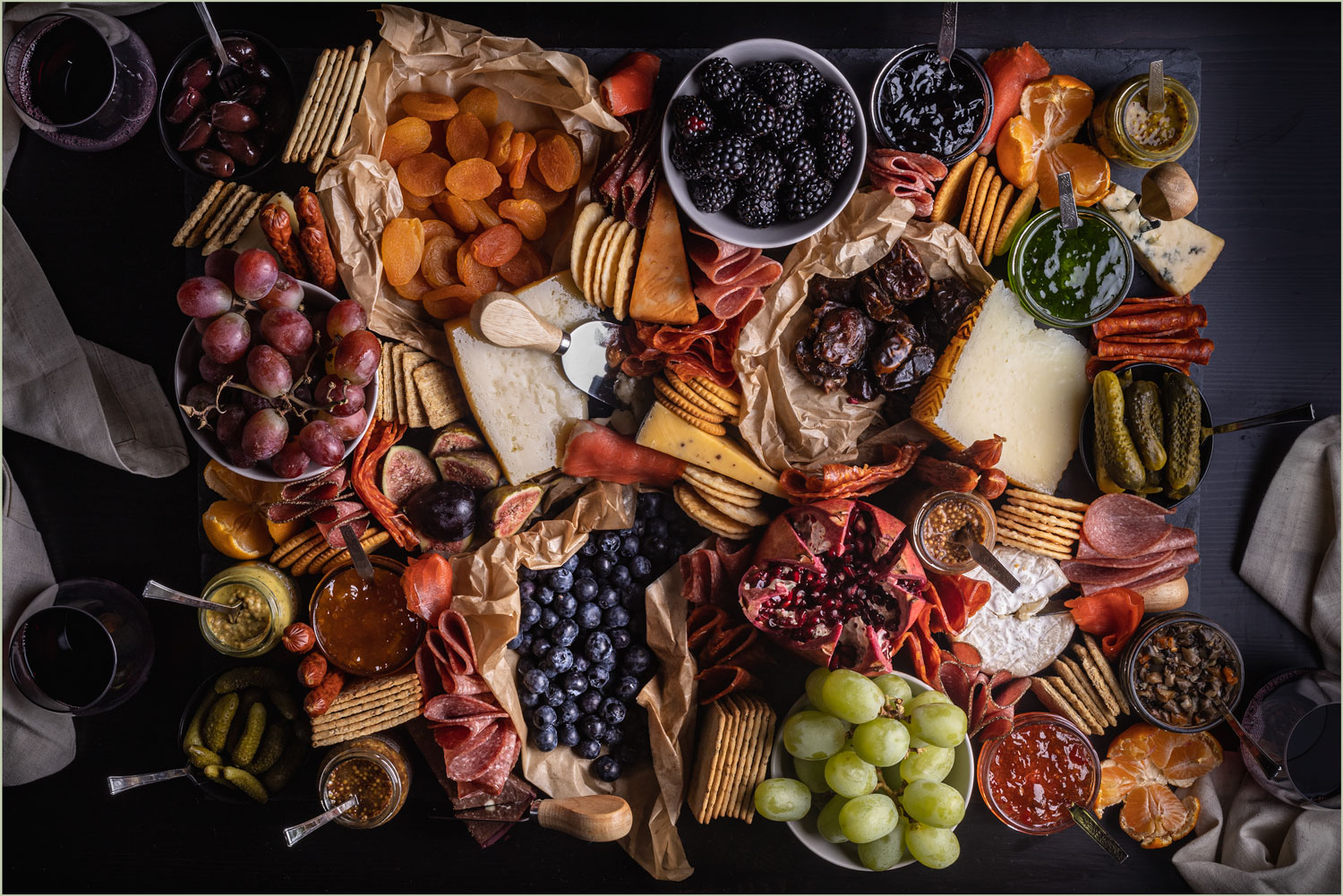 A giant charcuterie board willed with a variety of fruits, cured meats, cheeses, spreads and a crackers.