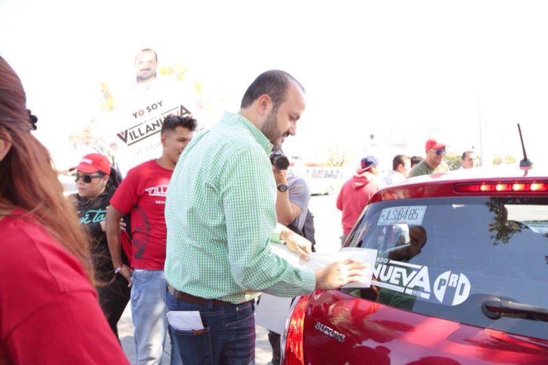 El candidato del PRI por Guadalajara, Ricardo Villanueva, en una pega de calcamonias para autos. Foto: Internet
