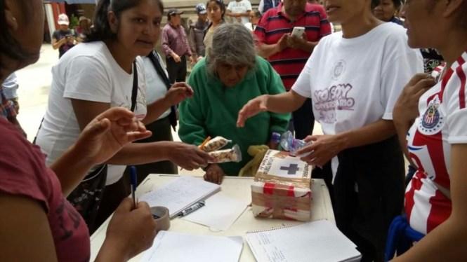 Una anciana ayuda a los maestros en uno de los puntos de donación. Foto: Facebook