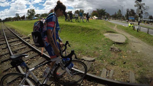 La única descripción es la vida. Mujer ciclista camina al lado de su bicicleta cruzando por la carrilera del tren en un día soleado.