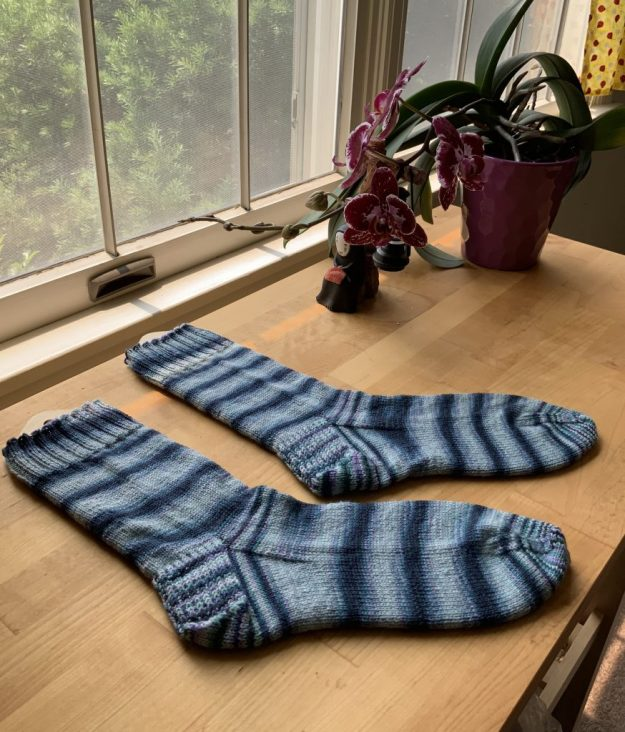 Socks in almost self-striping pattern of dark and light blue