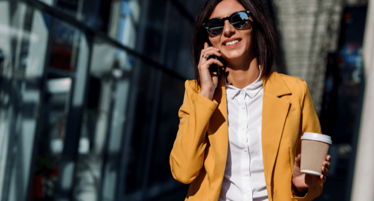Professional woman in a yellow suit, white button down holding a coffee while taking a phone call