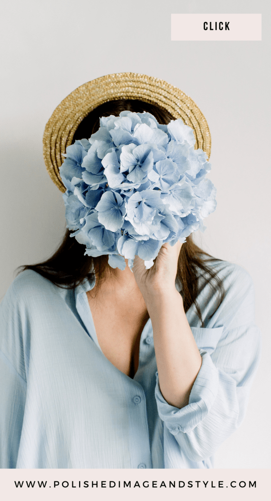 Woman holding a blue bouquet in front of her face