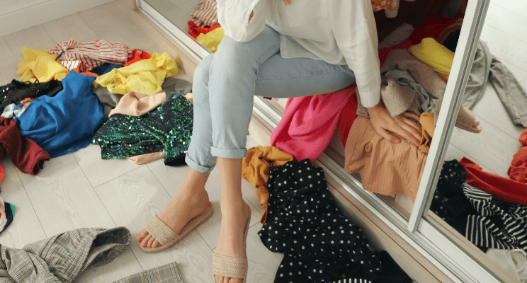Woman sitting in her closet that is a mess with clothing scattered across the ground