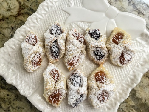Kolaczki - Polish Cookies with fruit filling on white platter on slab of granite