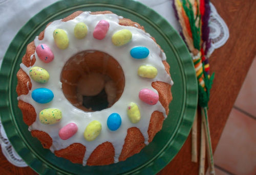 easter babka on green cake plate topped with white glaze and candy eggs