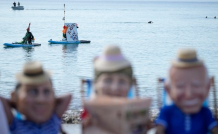 """Paddleboarders go by with a banner which reads """"no plastic"""" as climate activists from Oxfam, wearing giant heads depicting the leaders of the G7, sit on beach chairs as they participate in an action on Swanpool Beach in Falmouth, Cornwall, England, Saturday, June 12, 2021. Leaders of the G7 gather for a second day of meetings on Saturday, in which they will discuss COVID-19, climate, foreign policy and the economy. Leaders depicted from left, French President Emmanuel Macron, German Chancellor Angela Merkel and U.S. President Joe Biden. (AP Photo/Alastair Grant)"""