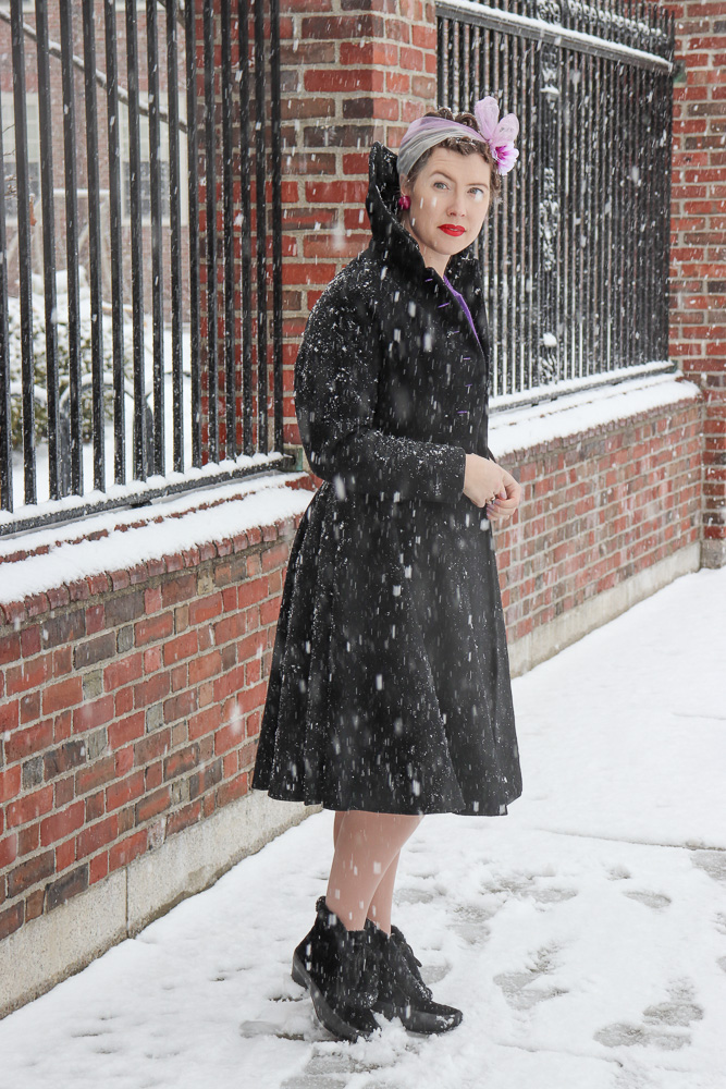 Woman wearing a black princess coat and black reproduction boots in the snow