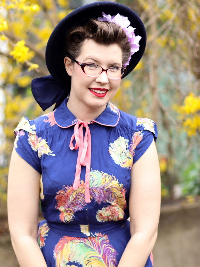 Frances wears a large blue felt hat with purple flowers tucked under the brim and a blouse with puffed sleeves and a small bow at the neckline.