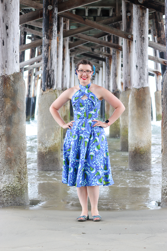 A girl stands under a pier wearing the Charm Patterns Lamour Dress in a blue jellyfish cotton with the straps crossed in front