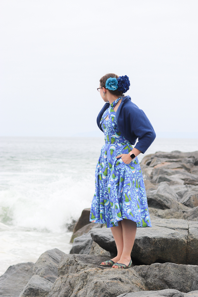 A girl stands on a breakwater wearing a jellyfish-print retro sun dress and a blue fleece bolero