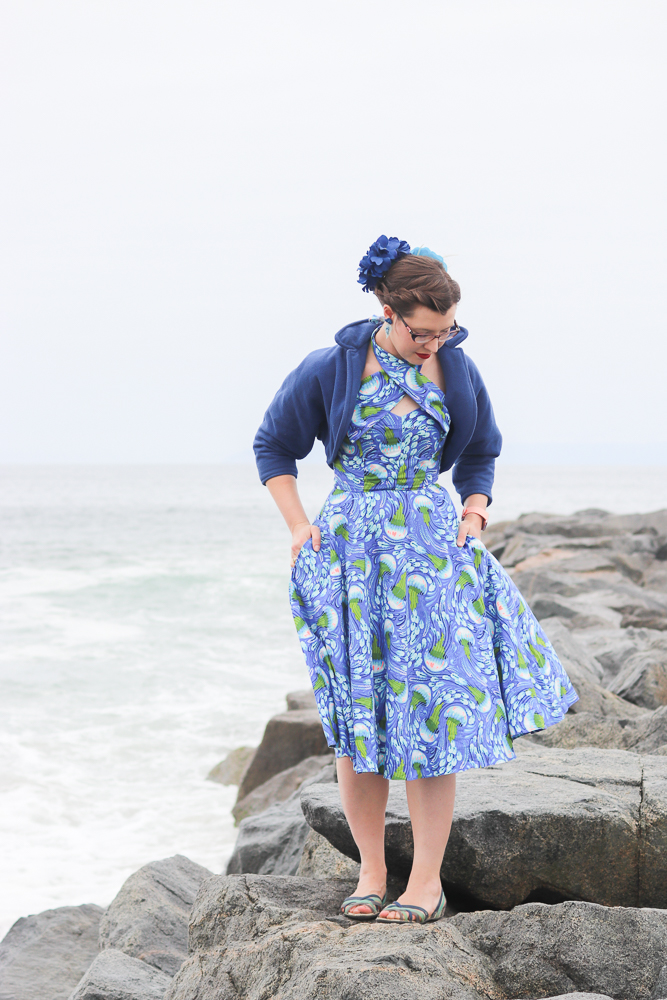 A girl stands on a breakwater wearing a jellyfish-print retro sun dress and a blue fleece bolero