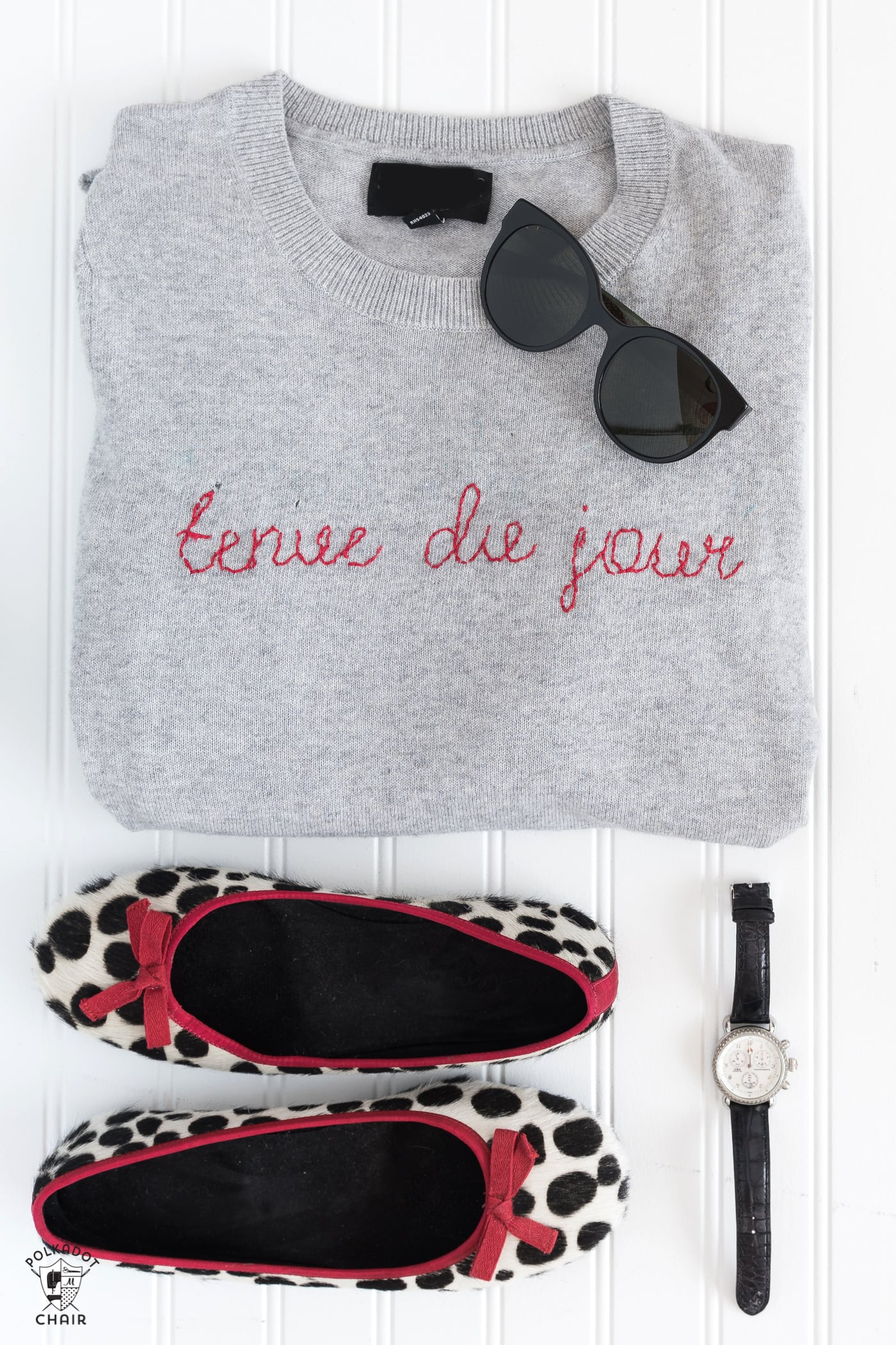 Learn how to make a DIY Embroidered sweater with a fun french quote on it. Includes free embroidery pattern for the quote. A clever way to refashion an old sweater. #DIYEmbroidery #DIYFashion #embroideredsweater #tutorial