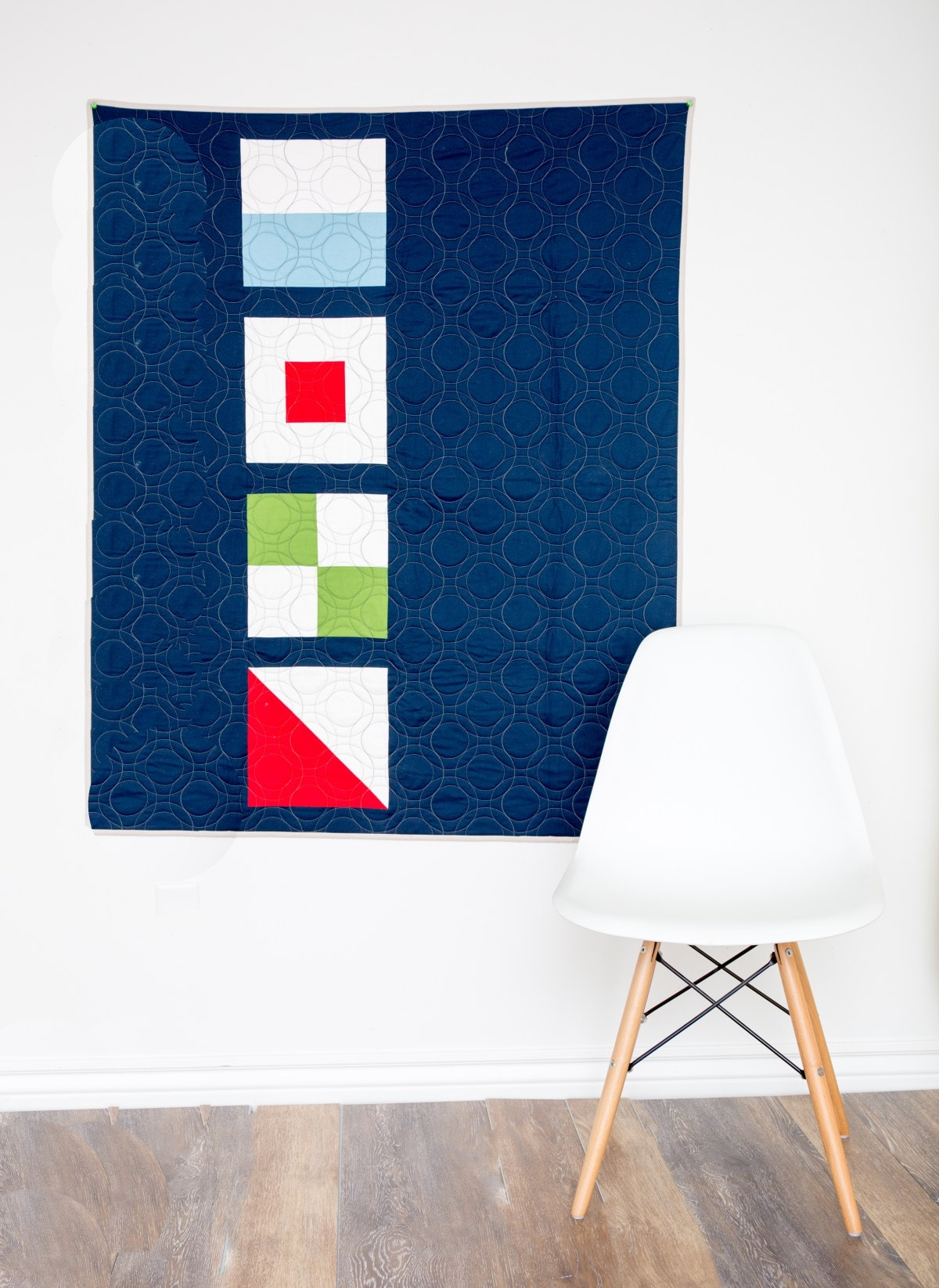 quilt on wall with chair