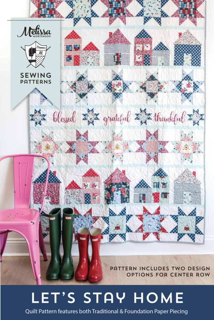 pattern cover of let's stay home quilt. quilt on white wall with pink chair in foreground