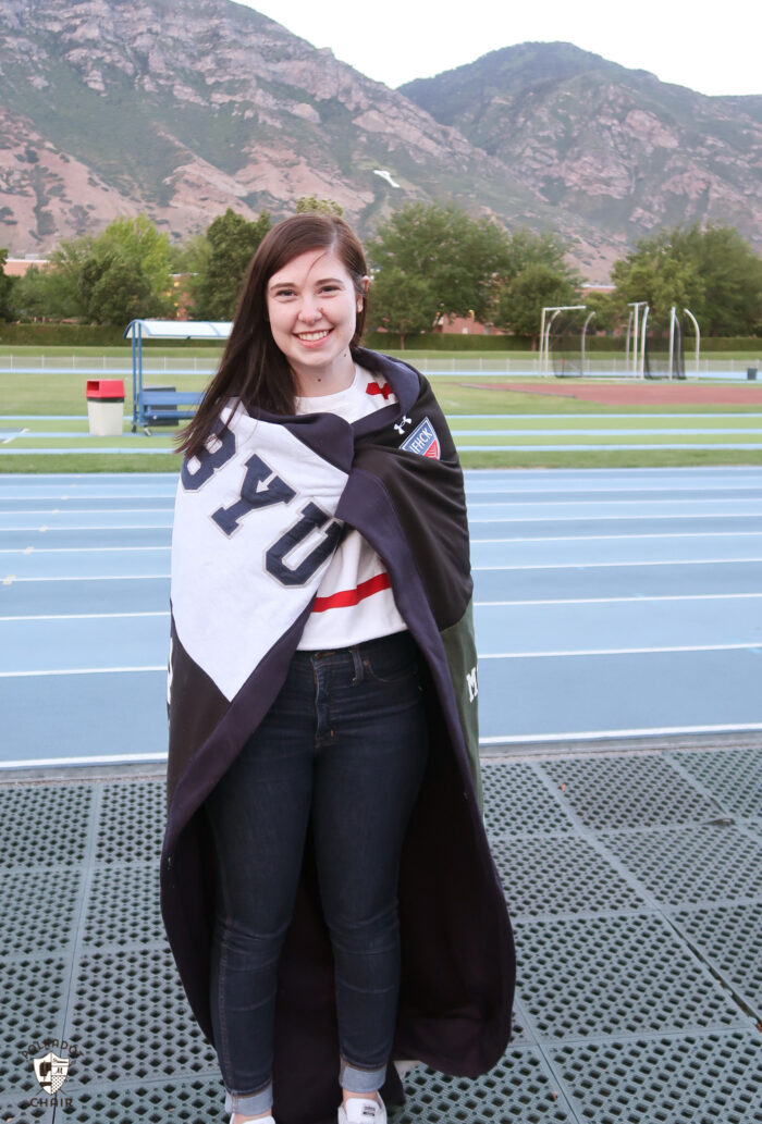 Girl with sweatshirt blanket at track and field