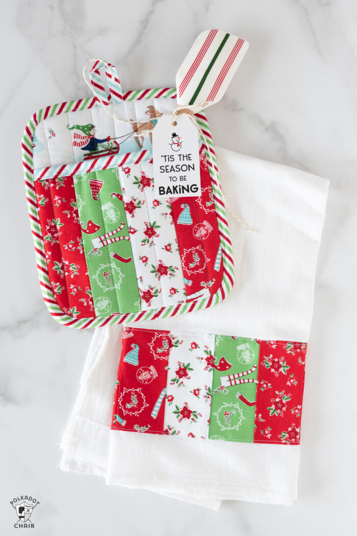 Striped potholder and Christmas dishtowel on white marble table