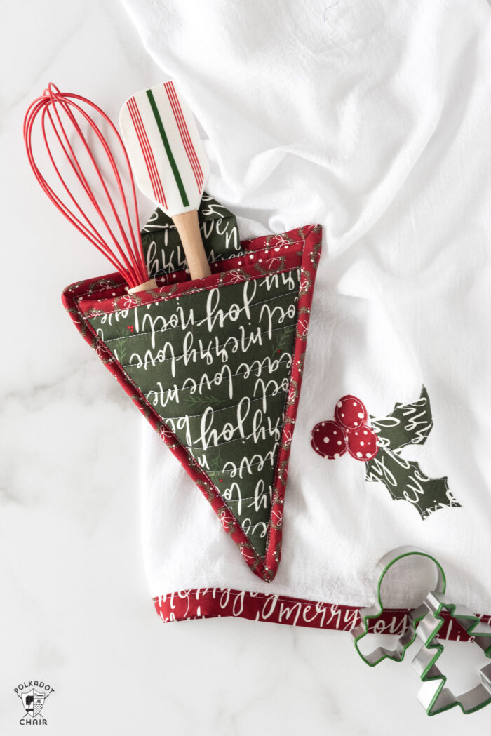 Christmas Tree potholder with whisk and spatula in pocket on table with kitchen towel.