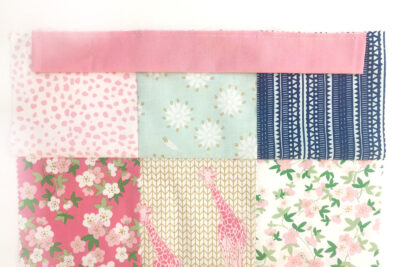 casing pinned to patchwork bag on white tabletop