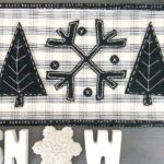 Black and white applique wool mat on gray table