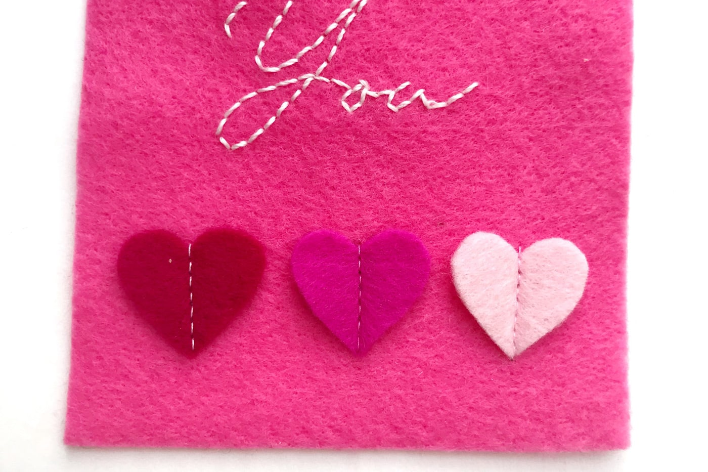hand embroidered felt gift tags on white table showing detail of stitched down hearts